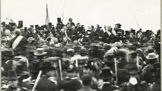 Lincoln giving his address at Gettysburg -- he's the one in the tall black hat.