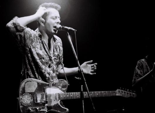 Joe Strummer, playing with the Pogues (photo by Masao Nakagami)