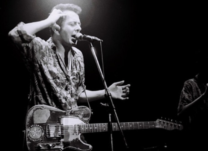 Joe Strummer, playing with the Pogues (photo by Masao Nakagami)